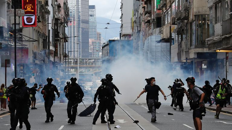 Riot police fire tear gas into the crowds to disperse anti-national security law protesters during a march at the anniversary of Hong Kong's handover to China from Britain in Hong Kong, China