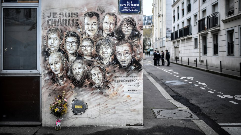 Policemen are seen next to a painting in tribute to members of Charlie Hebdo newspaper