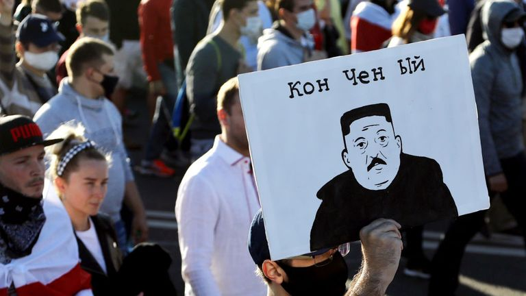 "A man carries a placard depicting Belarus' President as North Korean leader Kim Jong-un and reading ""Washed-up"" during a demonstration called by opposition movement for an end to the regime of authoritarian leader in Minsk on September 20, 2020 - Belarus President Alexander Lukashenko, who has ruled the ex-Soviet state for 26 years, claimed to have defeated opposition leader Svetlana Tikhanovskaya with 80 percent of the vote in the August 9, elections. (Photo by - / TUT.BY / AFP) (Photo by -/TUT"