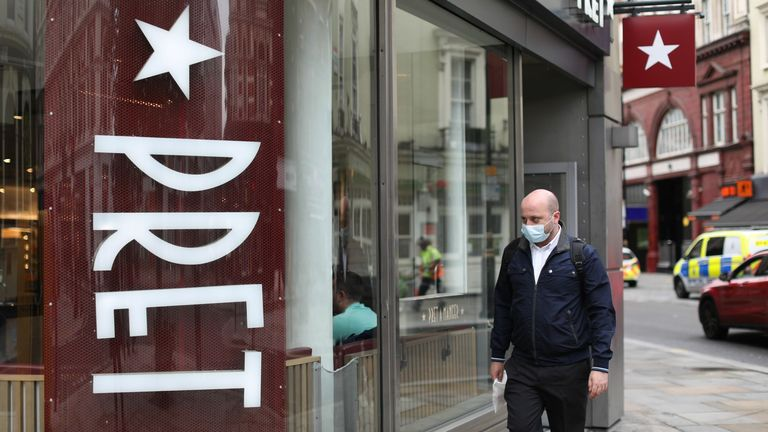 A man wearing a face mask as a precaution against the spread of the novel coronavirus walks past a Pret a Manger store in central London on August 28, 2020. - British coffee and sandwich chain Pret a Manger on August 27 said it was cutting 2,800 jobs as a result of the impact of the coronavirus outbreak.