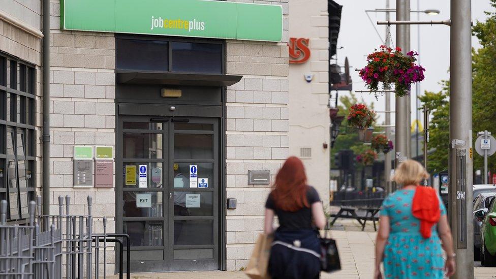 Two women walk past a job centre