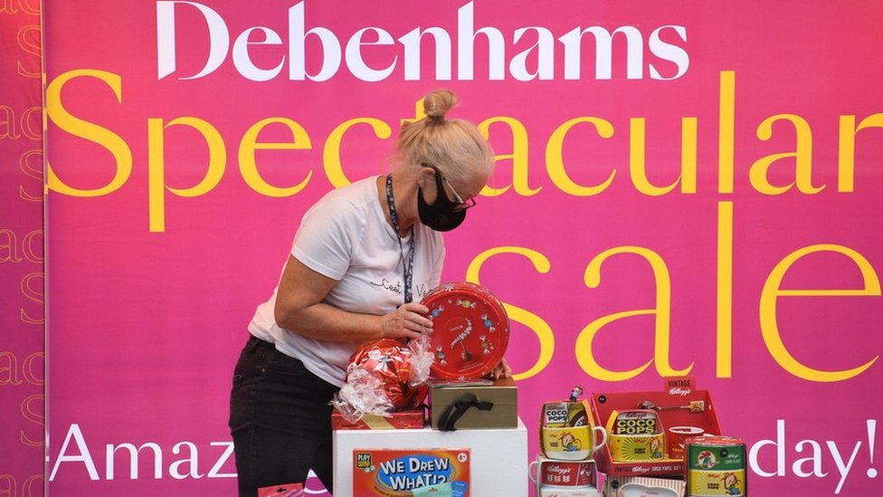 A shop assistant adjusts a window display in Debenhams in front of a sale sign