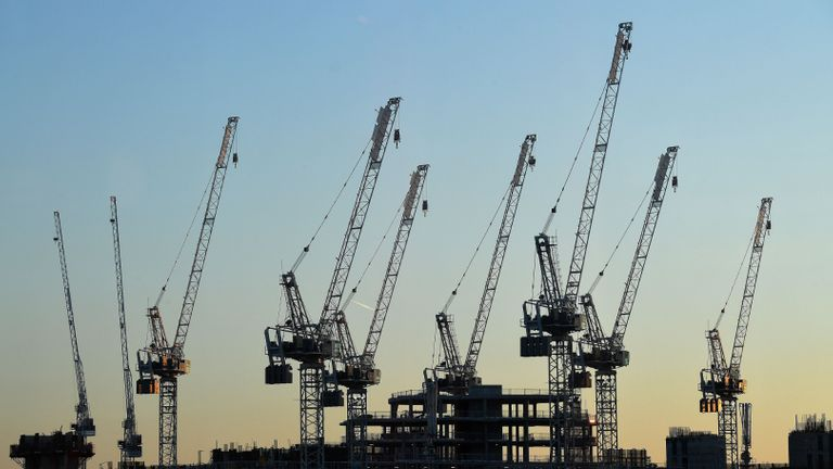 The sun sets beyond construction cranes standing over the building site for new apartments and a retail complex, at the Battersea Power Station redevelopment site in south London on May 14, 2020 following an easing of the novel coronavirus COVID-19 lockdown guidelines. - Prime Minister Boris Johnson has urged people to continue to work at home if they can but said those in sectors such as manufacturing and construction could return if it is safe. (Photo by JUSTIN TALLIS / AFP) (Photo by JUSTIN TALLIS/AFP via Getty Images)