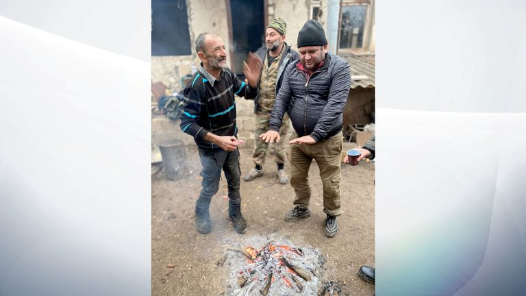 Some men warm their hands by a fire