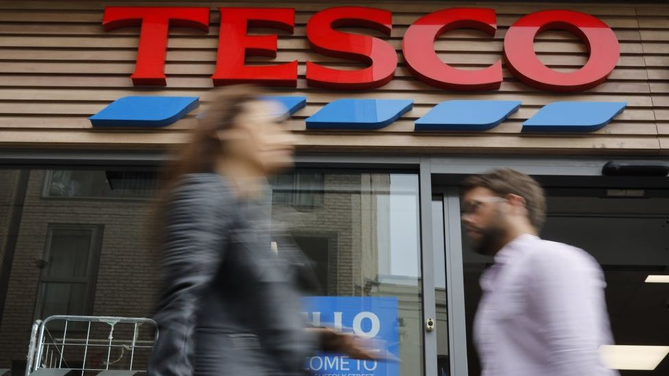 Two people walk past a Tesco store