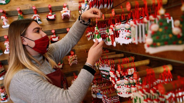 A shop assistant in a Christmas shop in Rome, Italy