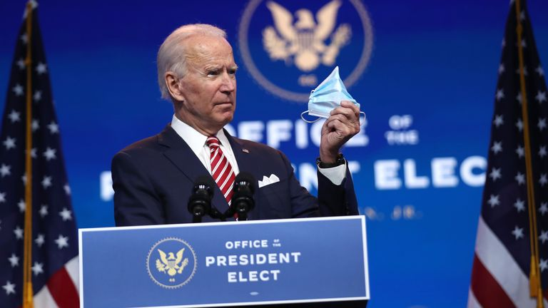 U.S. President-elect Joe Biden holds up a face mask as he delivers remarks about the U.S. economy during a press briefing at the Queen Theater on November 16, 2020 in Wilmington, Delaware