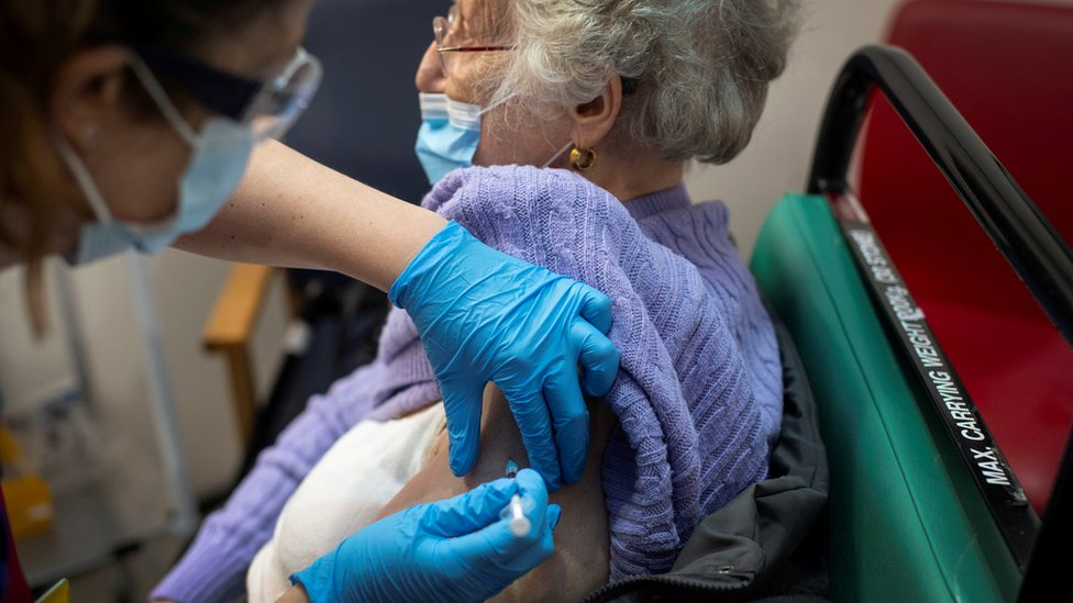 """A woman receives the first of two Pfizer/BioNTech COVID-19 vaccine jabs, at Guy""""s Hospital"""