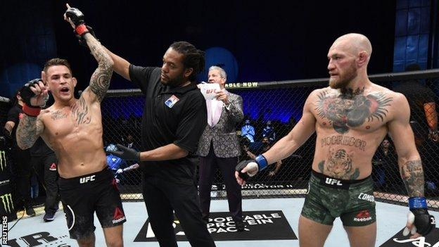 Dustin Poirier's hand is held aloft after beating Conor McGregor at UFC 257