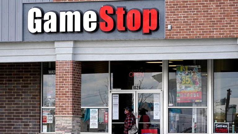 A woman wears a mask as she walks past a GameStop store in Des Plaines, Ill., Thursday, Oct. 15, 2020. GameStop is closing more stores than it originally planned, with the struggling retailer warning of more closures next year. (AP Photo/Nam Y. Huh)