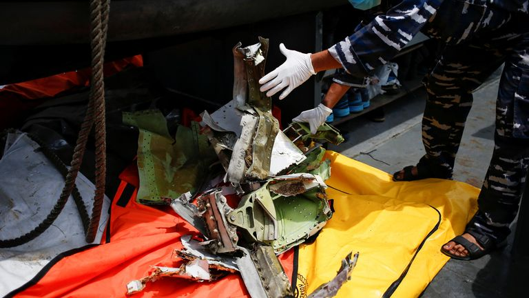 A member of the Indonesian navy inspects a piece of plane debris