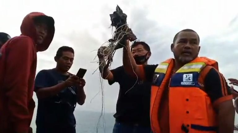 Indonesian divers discover body parts and pieces of fuselage after plane crash