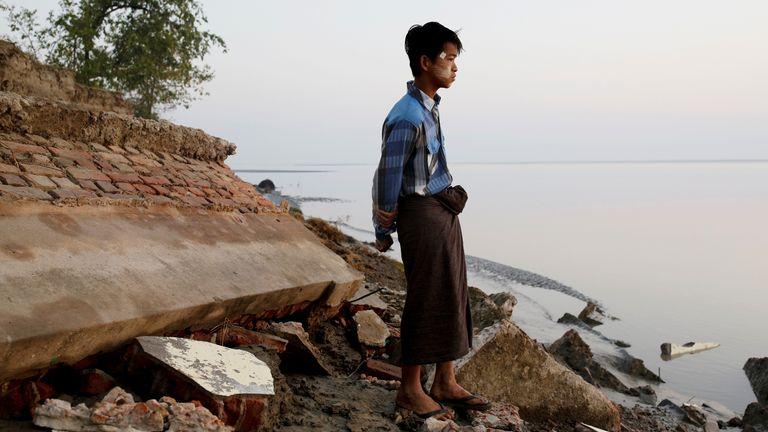 A student stands near the rubble of a school after it collapsed into the water in Myanmar