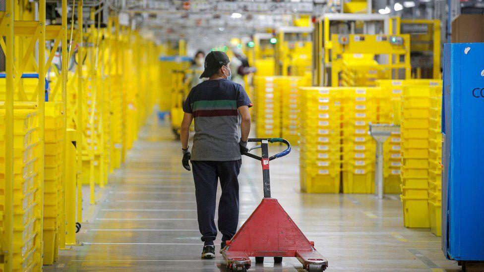 "An employee pulls a cart at Amazon""s JFK8 distribution center in Staten Island, New York, U.S. November 25, 2020."